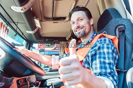 camionista seduto in cabina dando pollici