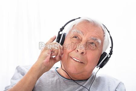 senior man listening to music on
