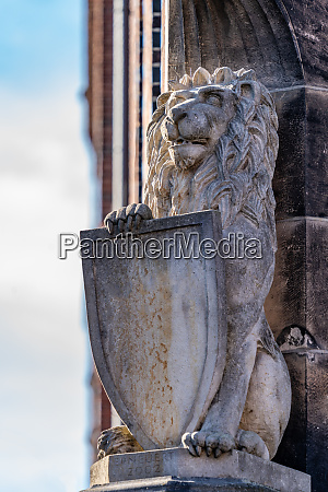carved stone lion with heraldic shield