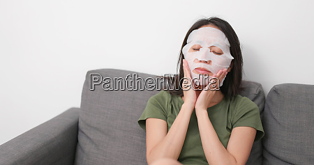 woman applying mask on face at