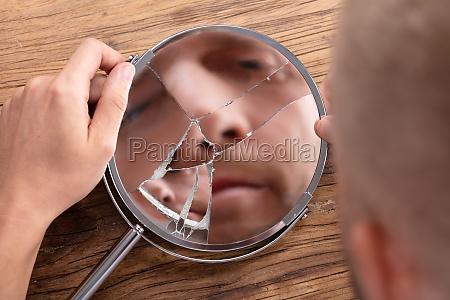 mans face in broken mirror
