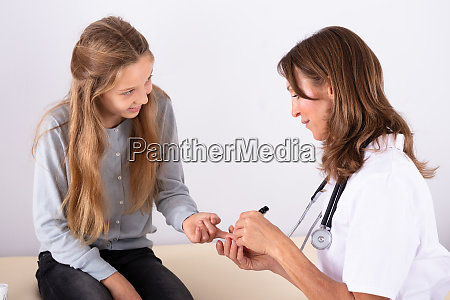 doctor checking girls blood sugar level