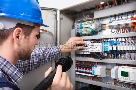 elettricista che esamina una scatola portafusibili