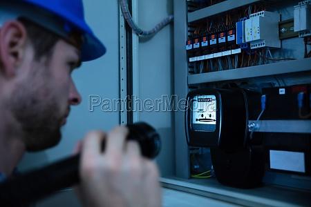 elettricista che esamina una scatola fusibile