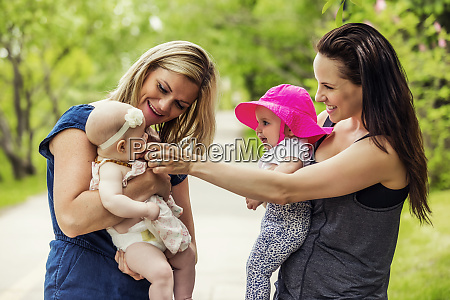 two young mothers pause while walking