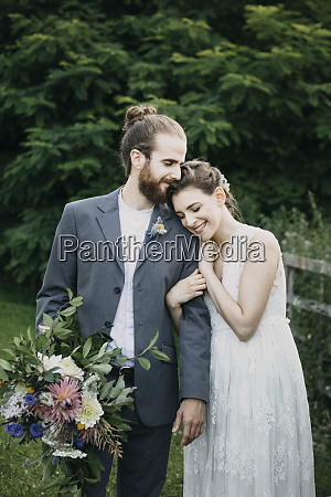 happy affectionate bride and groom standing