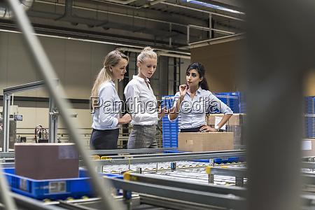 three women discussing at conveyor belt