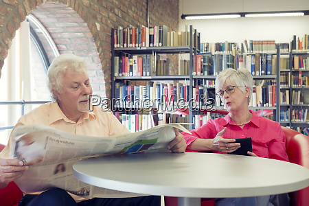 senior couple with newspaper and e