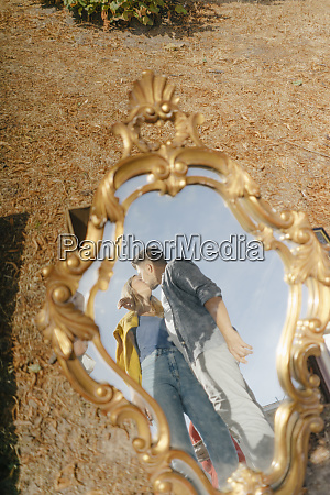 affectionate young couple kissing reflected in