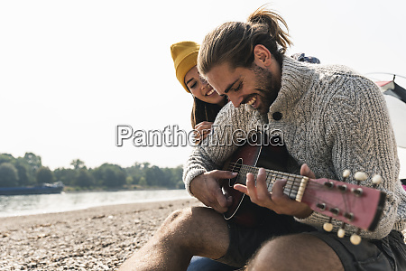 happy young couple with guitar at