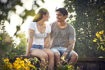 romantic young couple sitting on wall