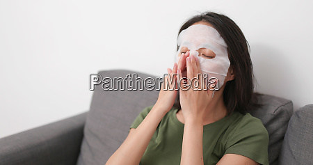 woman apply skincare mask on face