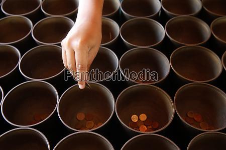 child offering coins in wat suandok