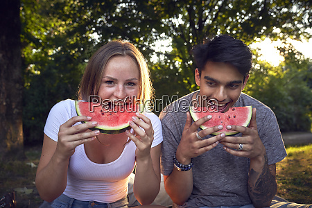 young couple sitting in park eating