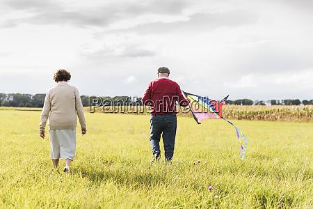 senior couple walking with kite in