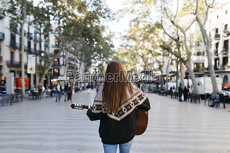 red haired woman playing the guitar