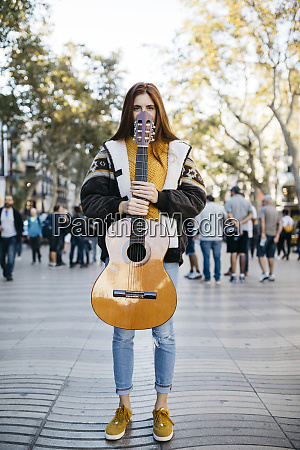 red haired woman holding a guitar