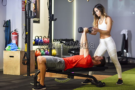 personal trainer assisting client with weight