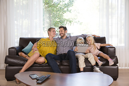 family sitting on couch at home
