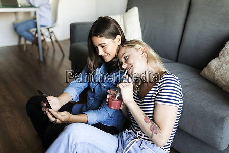 two smiling young women sitting on