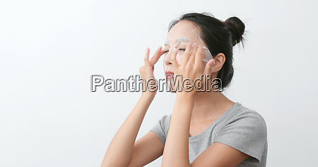 woman apply paper mask and massaging
