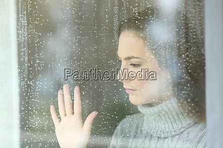 ragazza triste guardando attraverso una finestra