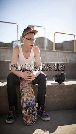 caucasian man sitting at skate park