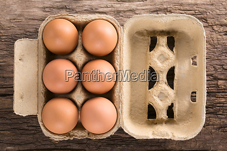 raw brown eggs in egg box