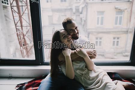 giovane coppia abbracciare dalla finestra dellappartamento