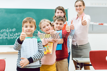 pupils and teacher showing thumbs up