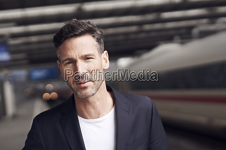 mature man with trolley on station