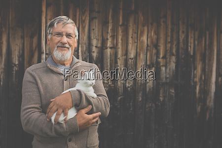 un uomo anziano tiene un gattino