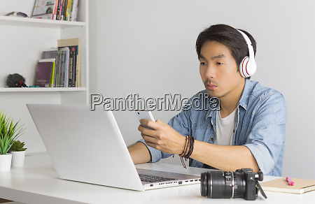 asian freelance videographer checking multimedia file
