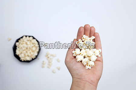 person holding popcorn in hand top
