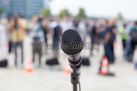 microphone in focus against blurred people