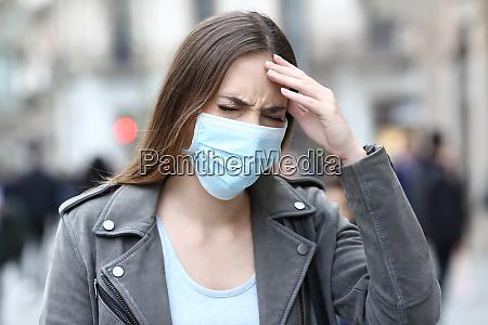 donna con maschera protettiva che soffre