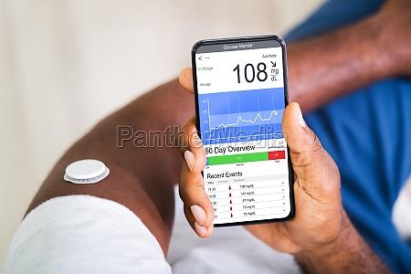 man checking blood sugar level on