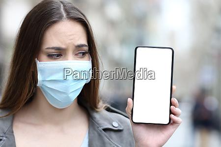 ragazza spaventata con maschera guardando schermo