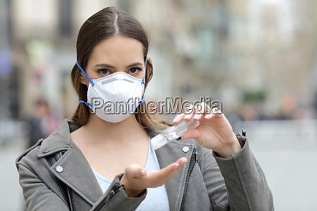 donna con maschera protettiva con disinfettante