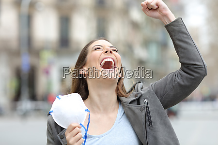 donna eccitata che celebra tenendo maschera