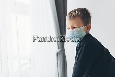 unhappy child wearing respiratory mask as