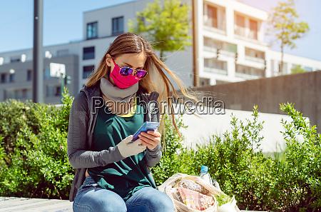 donna con maschera facciale seduta fuori