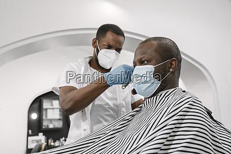 barbiere che indossa maschera chirurgica e