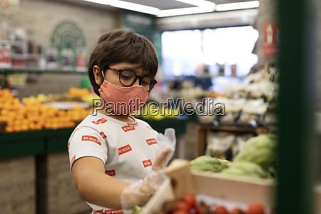 ragazzo che prende verdure al supermercato