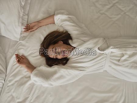donna anziana sorridente sdraiata sul letto