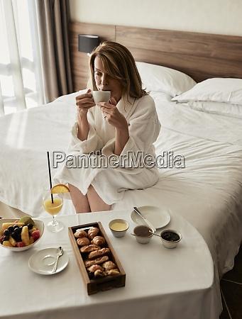donna anziana bionda che beve caffe